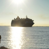 """Foto Nicoloro G. 17/10/2013 Porto Corsini ( Ravenna ) Al terminal di Porto Corsini (RA) è approdata la nave """" The World """", chiamata anche """" il condominio galleggiante """" perchè i 165 croceristi sono anche i proprietari delle lussuose cabine del valore di due milioni di euro. Batte bandiera delle Bahamas e sono queste le sue caratteristiche: 44.000 tonnellate di stazza, lunga 200 metri, alta 30 metri, 12 ponti, 165 appartamenti, 4 bar, 4 ristoranti, piscine, cinema, biblioteca, campo da tennis e da golf, un centro benessere. nella foto La nave """"The World"""" verso l'approdo"""