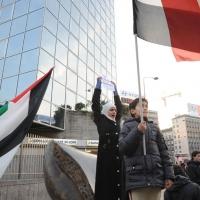 Foto Nicoloro G. 04/03/2011 Milano Manifestazione in piazza Loreto con corteo di un centinaio di immigrati libici contro il regime di Gheddafi a cui hanno partecipato anche immigrati tunisini ed egiziani. nella foto Donna manifestante con cartello e Bimbo manifestante con bandiera